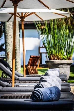 Poolside and beach side lounge chairs ad lounge beds with sun umbrellas in a tropical climate
