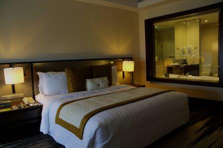 mooie slaapkamer in condomunium, appartement, huis met tweepersoonsbed en verlichting en meubels Stockfoto
