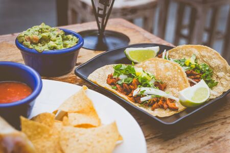 Al Pastor Tacos with roasted pork, spring onions and lemon wedges on the side, with tortilla chips and guacamole