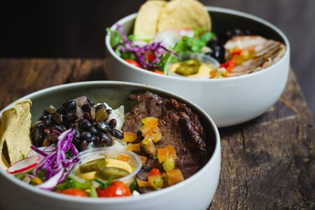 Protein Bowl of grilled Striploin, pilaf rice, beans, guacamole, homemade spiced cheese sauce, jalapenos & corn chips