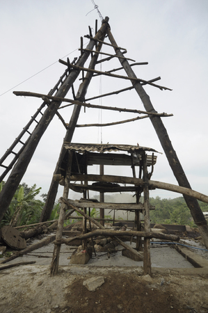 JAVA, INDONESIA - November 29, 2008: An oil derrick surrounded by environmental pollution and destruction caused by an illegal oil field on November 29, 2008 in Kadewan, East Java, Indonesia.
