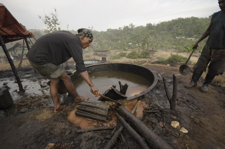 toxins: JAVA, INDONESIA - November 29, 2008: Unidentified oil workers collect unrefined crude oil at an illegal oil field on November 29, 2008 in Kadewan, East Java, Indonesia.