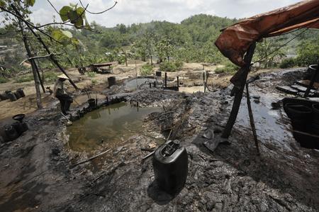 oil well: Java, Indonesia - 30 noviembre 2008: Un trabajador petrolero no identificado recoge sin refinar petr�leo crudo a un aceite ilegal as� el 30 de noviembre de 2008 en Kadewan, Java Oriental, Indonesia.