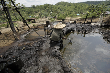 toxins: JAVA, INDONESIA - November 30, 2008: An unidentified oil worker collects unrefined crude oil at an illegal oil well on November 30, 2008 in Kadewan, East Java, Indonesia. Editorial