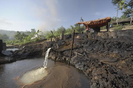 contaminacion ambiental: Java, Indonesia - 30 noviembre 2008: La contaminaci�n ambiental y la destrucci�n causada por un yacimiento de petr�leo ilegal el 30 de noviembre de 2008 en Kadewan, Java Oriental, Indonesia.