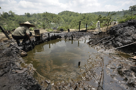 soil pollution: JAVA, INDONESIA - November 30, 2008: An unidentified oil worker collects unrefined crude oil at an illegal oil well on November 30, 2008 in Kadewan, East Java, Indonesia. Editorial