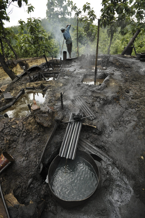 carcinogen: JAVA, INDONESIA - November 30, 2008: An oil worker refines crude oil by hand at a makeshift illegal jungle oil field on November 30, 2008 in East Java, Indonesia.