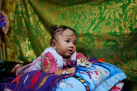 naming: BALI, INDONESIA - July 10, 2013: An unidentified 6-month-old baby girl poses after her Balinese-Hindu naming ceremony on July 10, 2013 in Ubud, Bali, Indonesia.