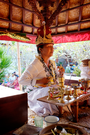 priestess: BALI, INDONESIA - May 23, 2014: A Balinese-Hindu priestess prays during a baby-naming ceremony on May 23, 2104 in Ubud, Bali, Indonesia. Editorial