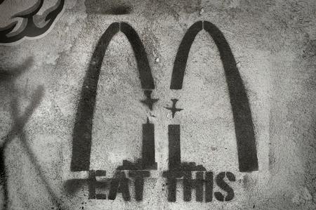 mocks: BALI, INDONESIA - January 29, 2014: Anti-American, anti-McDonalds graffiti mocks fast food and the twin towers terrorist attacks of 911 on January 29, 2014 in Ubud, Bali, Indonesia. Editorial