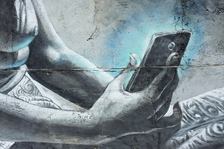 bare breasts: BALI, INDONESIA - December 5, 2015: Street art of a young, bare-breasted Balinese woman from an earlier era using a cell-phone on December 5, 2015 in Ubud, Bali, Indonesia.