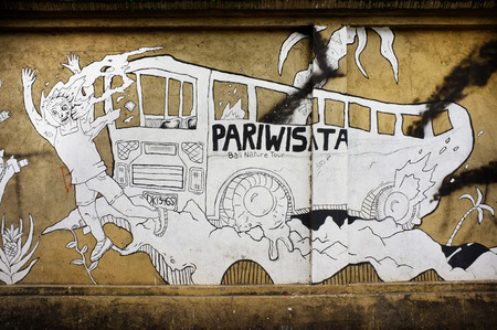 westerner: BALI, INDONESIA - December 24, 2015: Street art depicts a Western tourist being run over by a tourism bus, on December 24, 2015 in the tourism resort of Ubud, Bali, Indonesia.