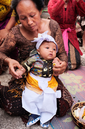 UBUD, INDONESIA - January 14, 2016: A 3-month-old Balinese-Hindu baby boy is dressed by his family in Hindu religious clothing during his baby-naming cermeony in Ubud, Bali, Indonesia. Editorial