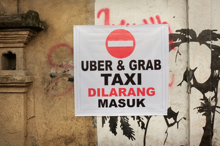 protest sign: BALI, INDONESIA - February 17, 2016: An unofficial protest sign on a wall in Indonesian objects to Uber and Grab taxi drivers reads Uber and Grab Taxis No Entry in the tourist village of Ubud, Bali, Indonesia. Stock Photo