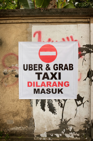 protest sign: BALI, INDONESIA - February 17, 2016: An unofficial protest sign on a wall in Indonesian objects to Uber and Grab taxi drivers reads Uber and Grab Taxis No Entry in the tourist village of Ubud, Bali, Indonesia. Editorial