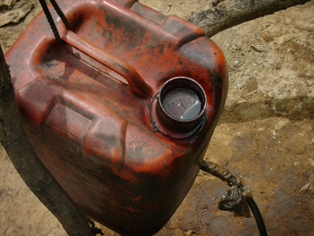 land pollution: Unrefined crude oil is collected in a jerry can at a heavily polluted, illegal oil field in Kadewan, East Java, Indonesia.