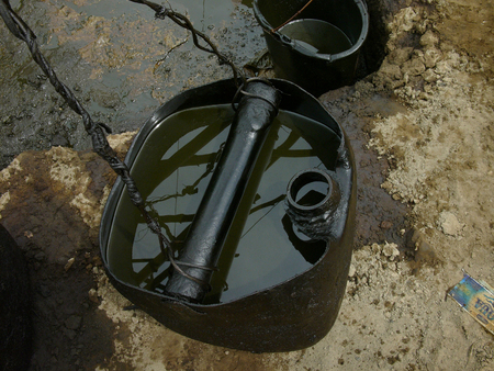 carcinogen: Unrefined crude oil is collected in jerry cans at a heavily polluted, illegal oil mine in Kadewan, East Java, Indonesia.