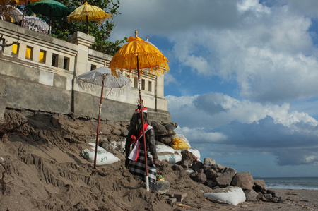 BALI, INDONESIA - JUNE 23: A Balinese-Hindu seaside temple damaged by freak waves and severe coastal erosion is protected with sandbags on June 23, 2016 at Batu Belig Beach, Bali, Indonesia. Stock Photo