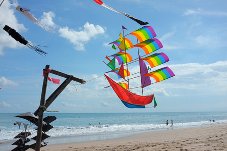 kuta: BALI, INDONESIA - JUNE 23: A kite in the shape of a sailing ship displays the LGBT flags rainbow colors on June 23, 2016 on a windy, sunny Kuta Beach in Bali, Indonesia.