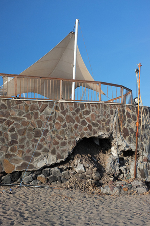 coastal erosion: BALI, INDONESIA - JUNE 23: The sea wall of a tourist restaurant and hotel lies damaged by freak waves and severe coastal erosion due to climate change on June 23, 2016 in Seminyak, Bali, Indonesia.