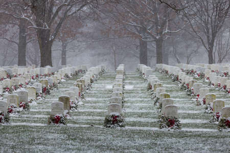 across america: Snow from the Blizzard of 2016 begins to cover the headstones and wreaths from Wreaths Across America at Arlington National Cemetery Stock Photo