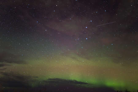 artificial satellite: Satellites, and stars, and the northern lights (aurora borealis) put on a show in the sky over Fairbanks, Alaska