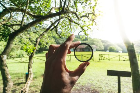 Hand Holding Camera Lens Filter in Hand in Front of sunrise in a forest of Costa Rica
