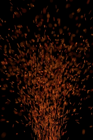Sparks flying upward on black background Imagens