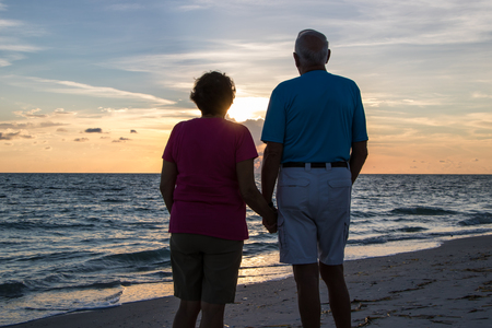 Man and a woman holding hands during sunset on a beach Imagens