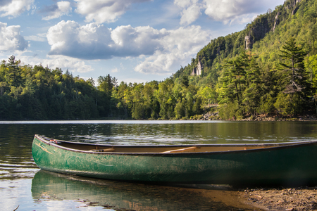 green canoe on the beach of Chapel Pond in Keene Valley, New York Imagens