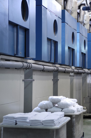 an industrial laundry with clean clothes before machine