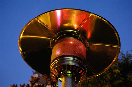 high section: Close up of a patio heater. Focus is on the flame, day