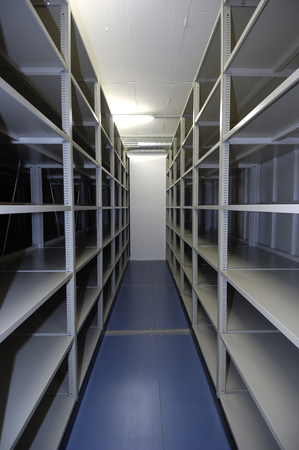 office cubicle: An empty storage unit with shelving on both walls -- a popular storage solution for city dwellers with limited space.