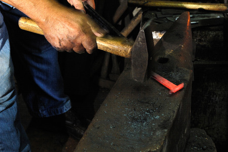 blacksmith shop: Blacksmith forges iron in the forge Stock Photo
