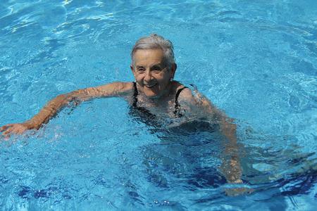 Hogere vrouw die pret in zwembad