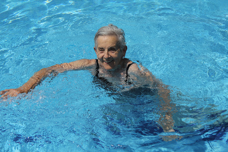 Senior Woman Having Fun In Swimming Pool