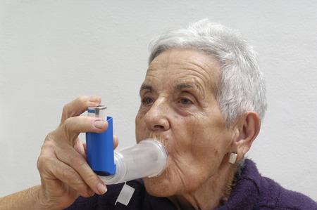 inhaler: old woman with an inhaler Stock Photo