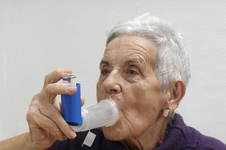 asthmatic: old woman with an inhaler Stock Photo