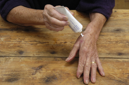on hands: Elderly woman putting on ointment