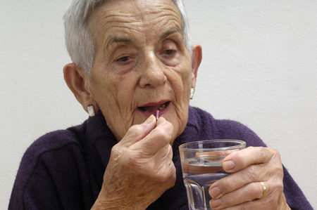 mature adult: senior woman taking pills