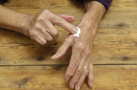 lady hand: Elderly woman putting on ointment