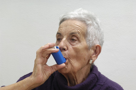 old woman with an inhaler Фото со стока