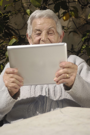 70s adult: old woman with tablet
