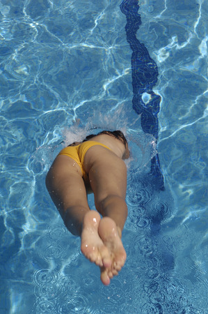taking the plunge: girl jumping in the pool a summer day