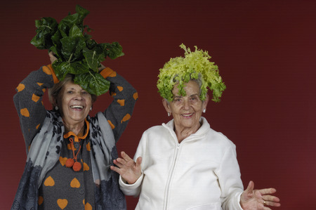 endive: Two senior women playing with chard and endive