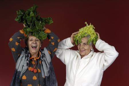 Two senior women playing with chard and endive