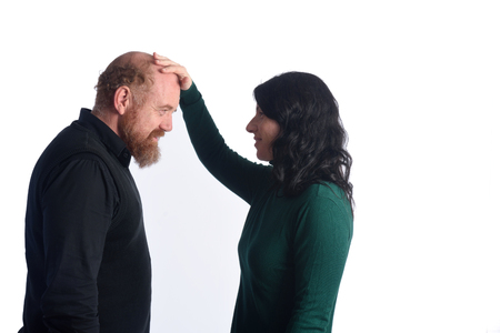 A woman touching the baldness of a man