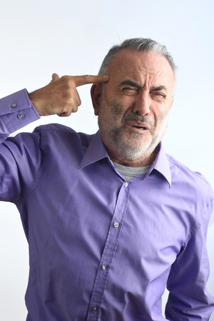 age 60: A man shooting with a finger on his head