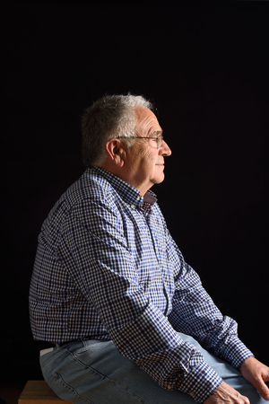 70 75: Portrait of a senior man with black background