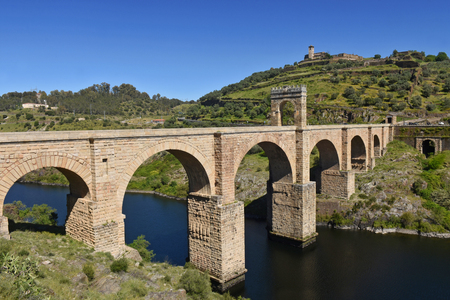 Roman bridge over the Tajo river in Alcantara, Caceres province, Extremadura, Spain Фото со стока
